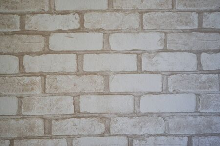 Old stucco molding in a side of bricks. The texture of the wallpaper in bright colors.