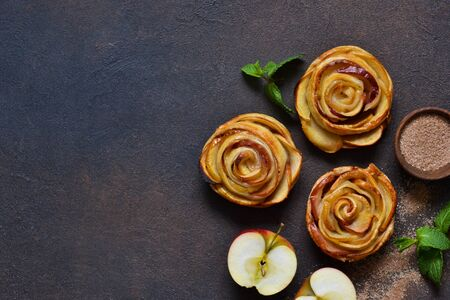 Dish of apple roses baked in puff pastry on a dark concrete background with apples. View from above Stok Fotoğraf