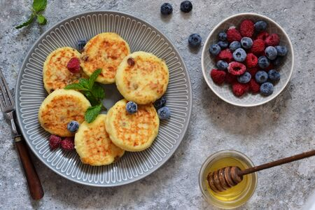Cheesecakes with berries and honey for breakfast on a gray concrete background. View from above. Zdjęcie Seryjne