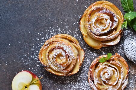 Dish of apple roses baked in puff pastry on a dark concrete background with apples. View from above Stock Photo