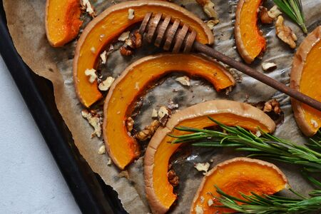 Baked sweet pumpkin with honey and rosemary on a tray on a gray concrete background. View from above. Stock Photo