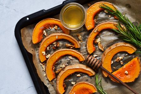 Baked sweet pumpkin with honey and rosemary on a tray on a gray concrete background. View from above. Stok Fotoğraf