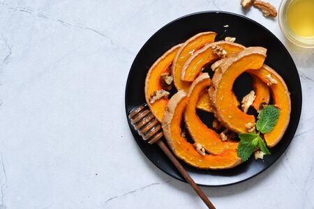 Baked sweet pumpkin with honey and rosemary on a gray concrete background. View from above.