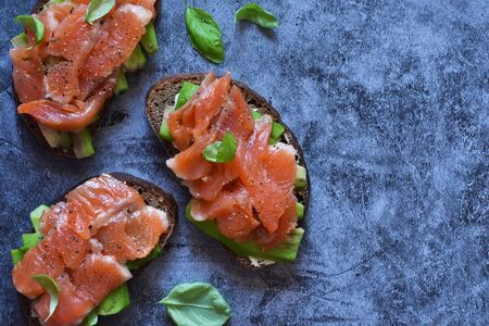 Sandwich with avocado and salmon on a concrete background. View from above. Reklamní fotografie