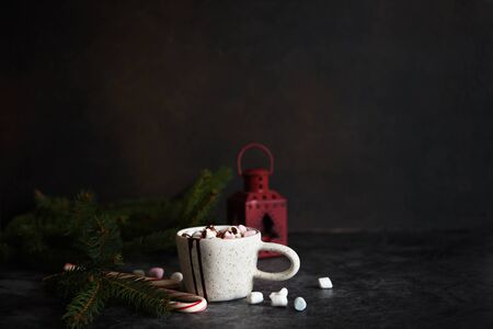 Hot chocolate with marshmallows on a dark concrete background. New Year card.