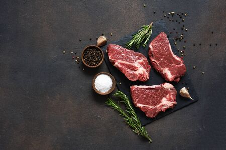 Raw marbled beef steak on a stone board. Spices, dishes. Top view flat lay with copy space.