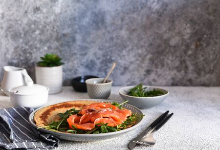 Crepe with arugula and salmon for breakfast on the kitchen table. Good morning.
