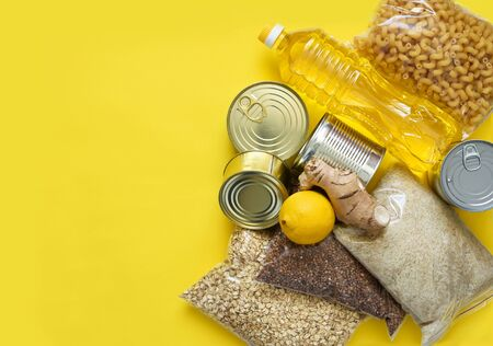 Food donations on a yellow background: oil, buckwheat, sugar, canned food. Sit at home. Quarantine.