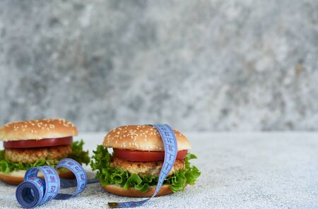 Big burger and with centimeter on a concrete background. Big calories. Fitness.