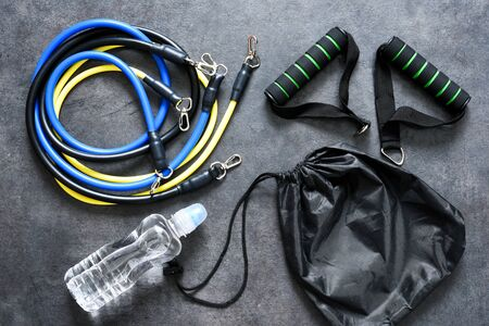 Sports accessories - an expander with a carbine and water on a black background. Fitness. Standard-Bild