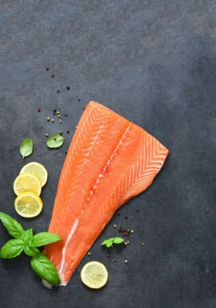 Raw salmon filet on a black background with lemon and basil.Flatly food.