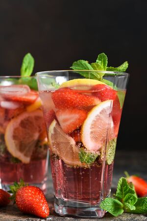 Lemonade with strawberries and mint on a dark concrete background. Summer cold drink.
