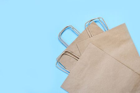 Set of craft paper bags for shopping on a blue background.Flatly.Gift bag.