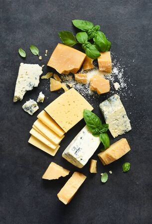 Cheese set: brie, blue cheese, parmesan and basil on a black concrete background. View from above.