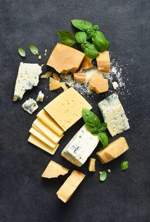 Ensemble de fromages : brie, fromage bleu, parmesan et basilic sur fond de béton noir. Vue d'en-haut.