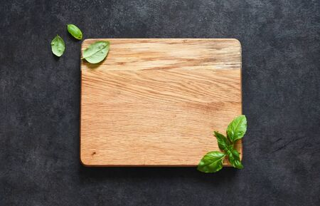 Cutting board and basil on a black stone background. Food background with place for text. View from above