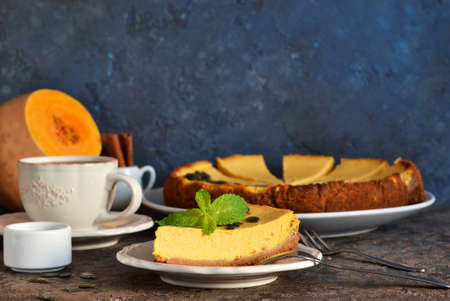 Slice of pumpkin cheesecake with a cup of coffee on a concrete background.