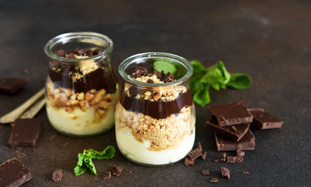 Dessert in a glass. Cheesecake with chocolate in a glass on a dark, concrete background.