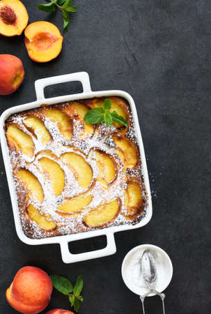 Delicate cake with peaches sprinkled with powdered sugar on a black concrete background