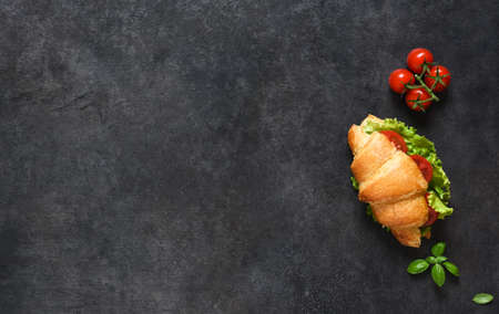 Breakfast with Croissant sandwiches with Salad Leaves, ham and Cherry Tomatoes, with sauce on a black background. View from above.