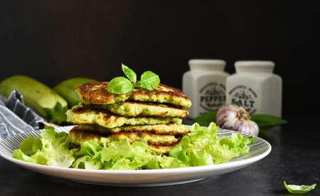Zucchini pancakes with sauce and garlic on a concrete black background. Zdjęcie Seryjne