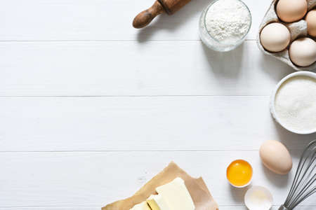 Baking ingredients: flour, eggs, sugar with a rolling pin on a light white wood background. With copy space.