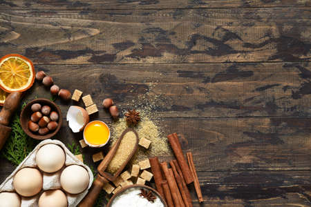 Ingredients for Christmas baking on a wooden background. Recipe for Christmas cake. Food preparation products: eggs, butter, flour, sugar. Stock Photo