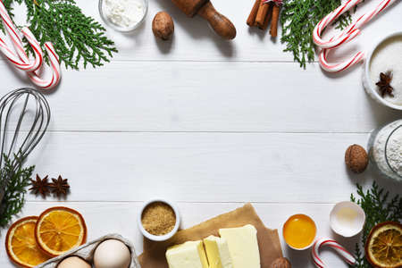 Ingredients for Christmas baking on a wooden white background. Christmas cookie recipe. Food preparation products: eggs, butter, flour, sugar.