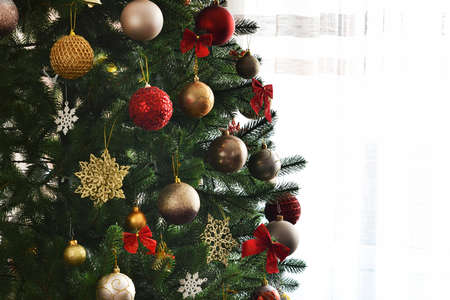 Christmas decoration. Christmas fir with balls of boxes with gifts in the room.