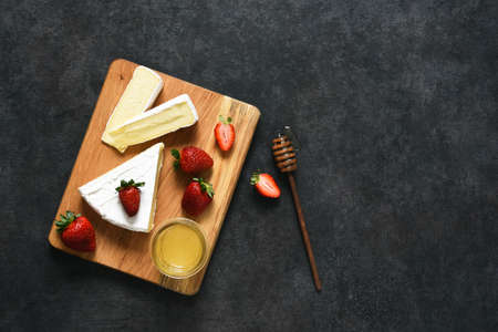 Brie cheese with strawberries and honey on a black kitchen table. View from above. Snack.