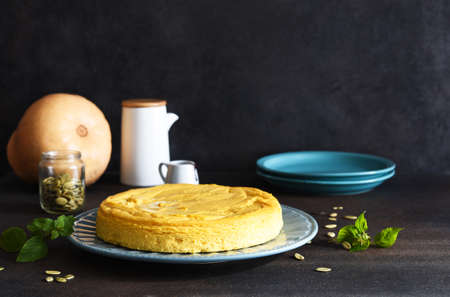 Homemade cheesecake with pumpkin on a dark concrete table. Horizontal focus.