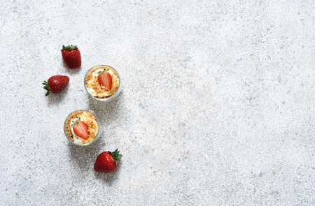 Dessert with crumbs, cream and strawberries. Cheesecake in a glass. Stock Photo