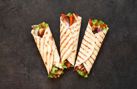 Mexican tortilla grilled wrap with chicken breast and vegetables on concrete background Stock Photo