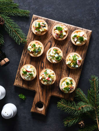 Tartlets with salad and champagne on the New Year's table. View from above.