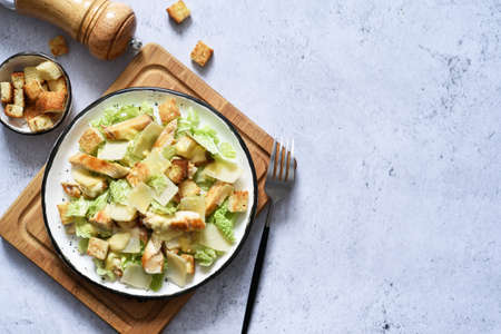 Caesar salad in a plate on a wooden board on a concrete background, top view.