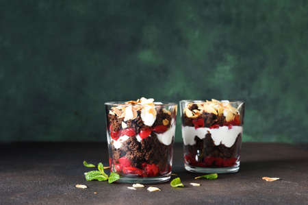Dessert black forest with cherries in a glass on a dark green background. Traditional German dessert. Horizontal focus.