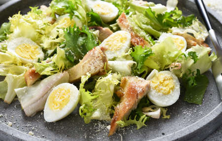 Caesar salad. Classic salad with chicken and parmesan on a concrete plate. Stock fotó