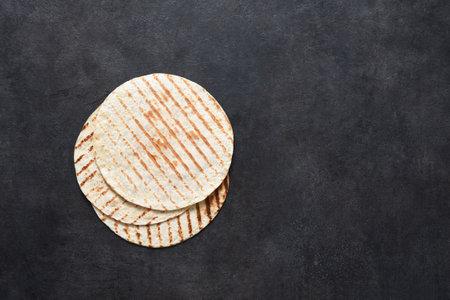 Grilled tortilla. Mexican flatbread - tortilla on a black concrete background.
