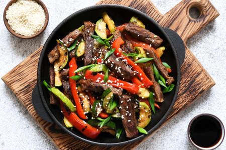 Frying pan with vegetables and beef and sesame seeds. Asian food. Imagens