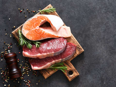 Raw beef steaks and salmon steak and rosemary on a board on a concrete background. 스톡 콘텐츠