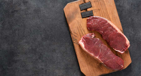 Steak, raw beef ribeye with spices on a wooden board. Cooking ingredients. View from above.