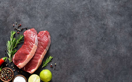 Steak, raw beef with spices, lime and chili on a black concrete background. Cooking ingredients. View from above. 스톡 콘텐츠