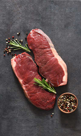 Steak, raw beef with spices and rosemary on a black concrete background. View from above.