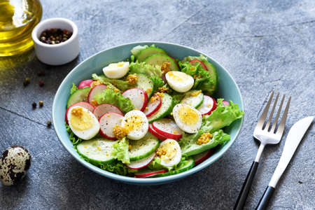 Vegetable, fresh salad with radish, egg and salad leaves in a blue plate on a concrete background.