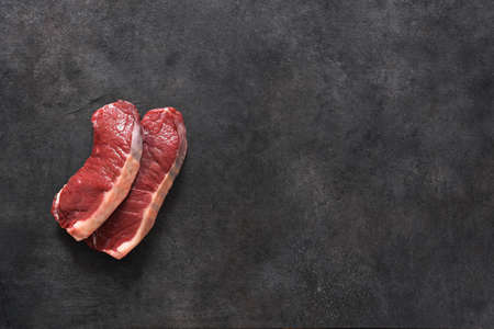 Raw beef steak on a black concrete background. View from above. 스톡 콘텐츠