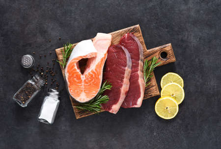 Raw beef steaks, salmon steak with spices and lemon on a board on a concrete background.