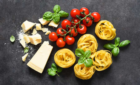 Tagliatele pasta, tomatoes, basil and parmesan cheese on a black concrete background. Ingredients for pasta with text space. Layout.