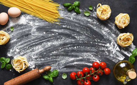 Flour, rolling pin, tomatoes and basil on the table. Pasta cooking process on the kitchen table. Ingredients for making pasta. 스톡 콘텐츠