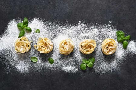 Tagliatelle pasta on a black concrete table. Cooking pasta on the kitchen table.