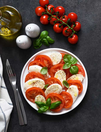 Caprese is a tomato and mozzarella appetizer. Traditional Italian salad on a black background with space for text. View from above.